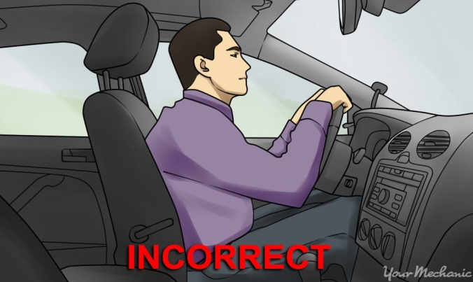 5 - How to Sit in a Car Without Back Pain - Man sitting too close to the steering wheel holding the wheel with elbows very bent